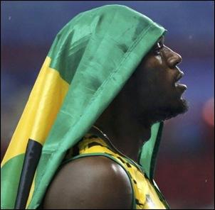 Bolt-cubre-su-cabeza-con-una-bandera-de-Jamaica.FABRIZIO-BENSCH-REUTERS-580x750