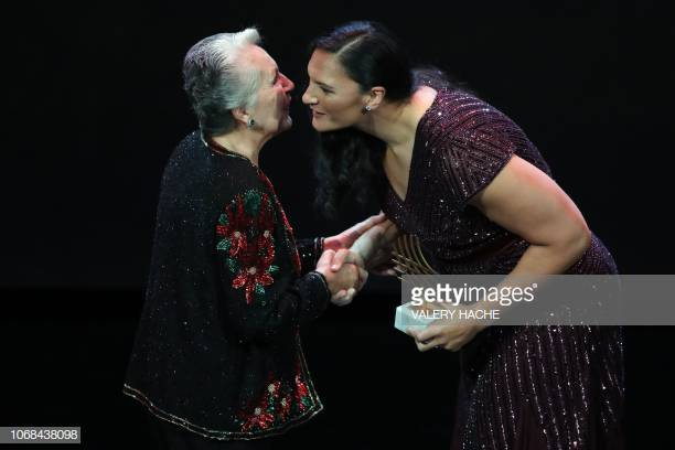Puerto Rico's General Secretary of the Association of Pan-American Athletics Evelyn Claudio Lopez (L) receives the Woman of the year award from New Zealand's athlete Valerie Adams during the IAAF athlete of the year awards ceremony, on December 4, 2018 in Monaco. (Photo by Valery HACHE / AFP) (Photo credit should read VALERY HACHE/AFP/Getty Images)